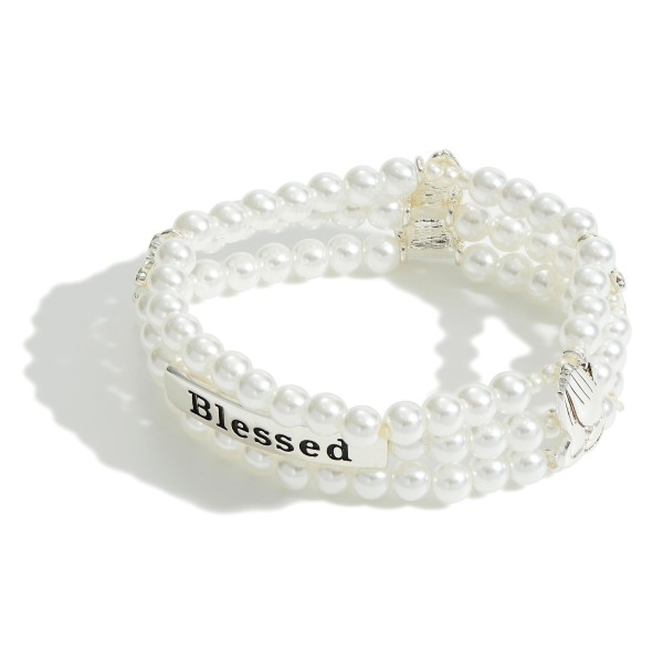"Triple Strand Faux Pearl Bracelet Featuring Cross Details and a Silver Bar that Says ""Blessed"".   - Approximately 2.5"" in Diameter"