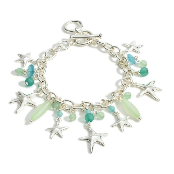 "Silver Chain Link Charm Bracelet Featuring Blue Bead Accents and Starfish Details.   - Approximately 2.5"" in Diameter - Toggle Closure"