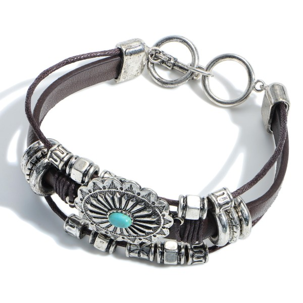 """Western Leather Bracelet Featuring an Oval Pendant and Turquoise Accents.   - Approximately 2.5"""" in Diameter - Toggle Bar Clasp"""