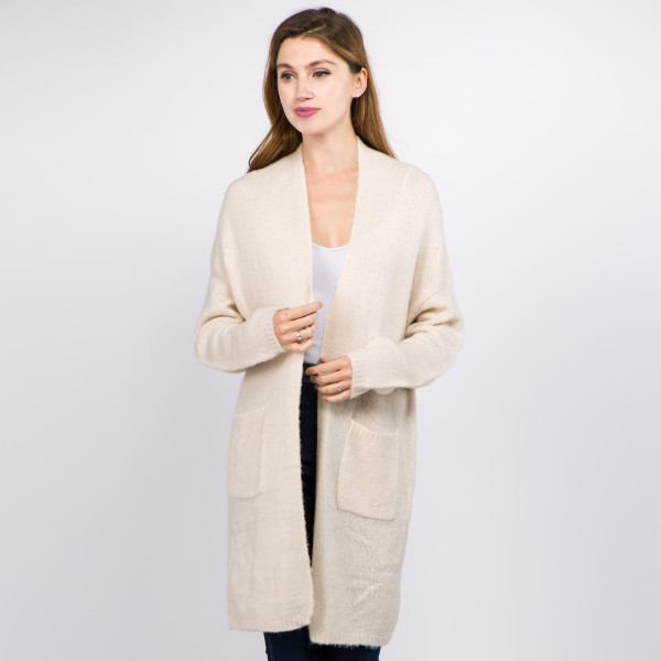 """Solid color soft touch knitted cardigan with front pocket details.  - One size fits most 0-14 - Approximately 35"""" in length - 70% Acrylic, 30% Polyamide, 3% Spandex"""