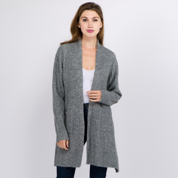 """Solid color ribbed knit cardigan with shark bite hem and pocket details.  - One size fits most 0-14 - Approximately 25"""" in back length; front hem 33"""" L - 66% Acrylic, 30% Polyester, 4% Spandex"""