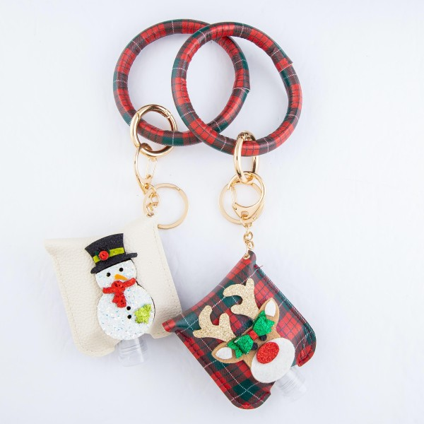 """PU Plaid Print Christmas Key Ring Hand Sanitizer Holder Bangle Wristlet Featuring a Raised Glitter Reindeer Design.  - Keyring to hold your keys - Can Be Worn as Wristlet - Detachable - Ring 3""""  - Fits up to 1fl.oz Sanitizer Bottle - Approximately 3"""" T x 2.5"""" W - (Approx) 10"""" L overall  ***Hand Sanitizer NOT INCLUDED. (Comes with empty Bottle)"""