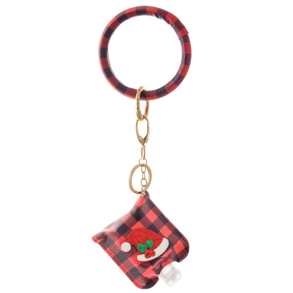 """PU Buffalo Check Christmas Key Ring Hand Sanitizer Holder Bangle Wristlet Featuring a Raised Glitter Santa Hat Design.  - Keyring to hold your keys - Can Be Worn as Wristlet - Detachable - Ring 3""""  - Fits up to 1fl.oz Sanitizer Bottle - Approximately 3"""" T x 2.5"""" W - (Approx) 10"""" L overall  ***Hand Sanitizer NOT INCLUDED. (Comes with empty Bottle)"""