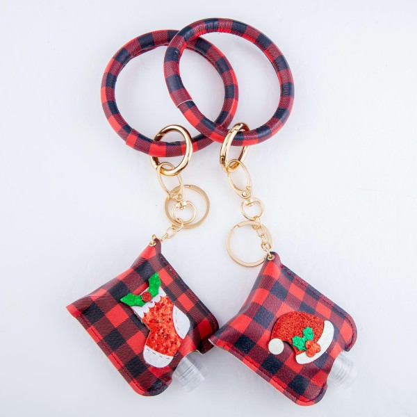 "PU Buffalo Check Christmas Key Ring Hand Sanitizer Holder Bangle Wristlet Featuring a Raised Glitter Santa Hat Design.  - Keyring to hold your keys - Can Be Worn as Wristlet - Detachable - Ring 3""  - Fits up to 1fl.oz Sanitizer Bottle - Approximately 3"" T x 2.5"" W - (Approx) 10"" L overall  ***Hand Sanitizer NOT INCLUDED. (Comes with empty Bottle)"