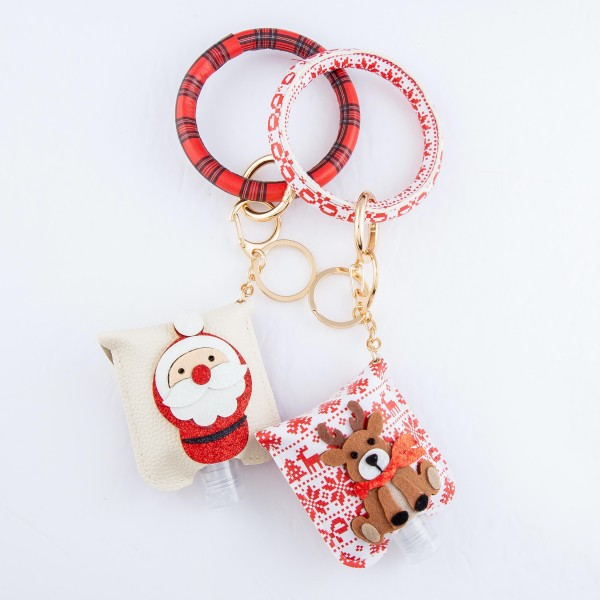 """PU Plaid Print Christmas Key Ring Hand Sanitizer Holder Bangle Wristlet Featuring a Raised Glitter Santa Design.  - Keyring to hold your keys - Can Be Worn as Wristlet - Detachable - Ring 3""""  - Fits up to 1fl.oz Sanitizer Bottle - Approximately 3"""" T x 2.5"""" W - (Approx) 10"""" L overall  ***Hand Sanitizer NOT INCLUDED. (Comes with empty Bottle)"""