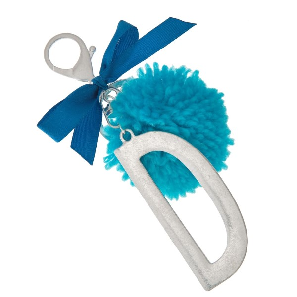 """Silver tone key chain or bag charm with a block 'D' initial pendant and blue pom pom. Approximately 5.5"""" in length."""