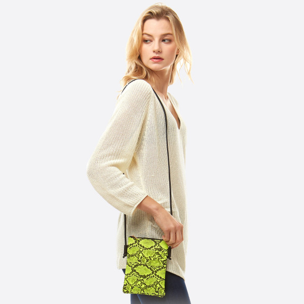 "Snakeskin print crossbody bag featuring:  - No inside pockets - One outside pocket  - Approximately 6"" W x 8"" T  - 100% PU"