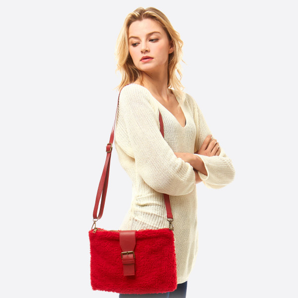 "Faux sherpa fleece crossbody/handbag featuring:  - Two inside separated pockets - One inside zipper pocket - Zipper closure - Faux leather magnetic belt detail  - Approximately 11"" W x 8"" T - 90% Polyester, 10% PU"