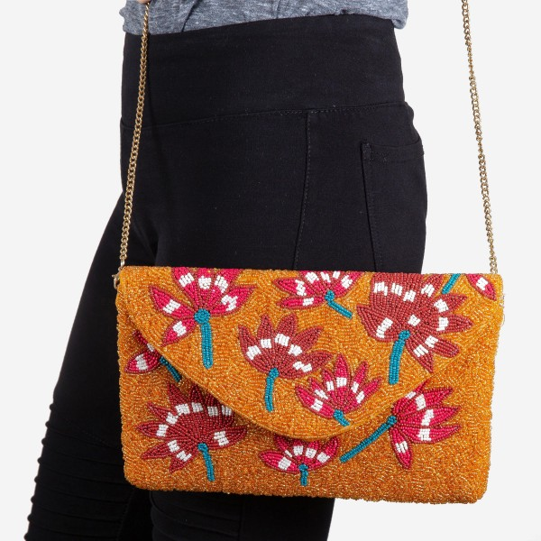 """High quality Orange oriental floral seed beaded crossbody clutch.  - Open (100% Cotton) lined inside - 1 inside open pocket - Fold over flap snap closure - Approximately 10"""" x 7""""  - Strap hangs approximately 26"""" L - 40% Seed Beads, 40% Cotton Canvas, 20% Metal"""