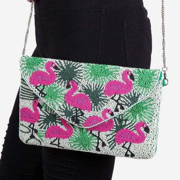"""High quality flamingo seed beaded crossbody clutch.  - Open (100% Cotton) lined inside - 1 inside open pocket - Fold over flap snap closure - Approximately 10"""" x 7""""  - Strap hangs approximately 26"""" L - 40% Seed Beads, 40% Cotton Canvas, 20% Metal"""
