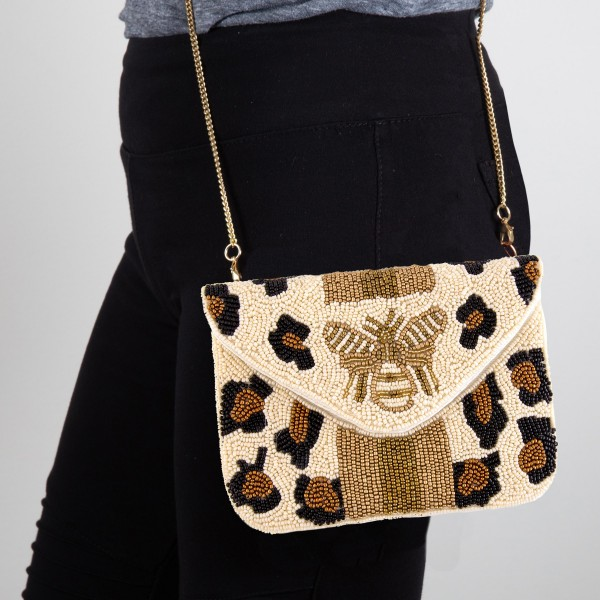 "High quality seed beaded leopard print designer inspired Bee crossbody clutch.   - Open lined inside  - 1 open functional pocket  - Fold over flap button closure  - Approximately 7"" W x 5"" T  - Strap hangs 22"" L  - 100% Cotton"