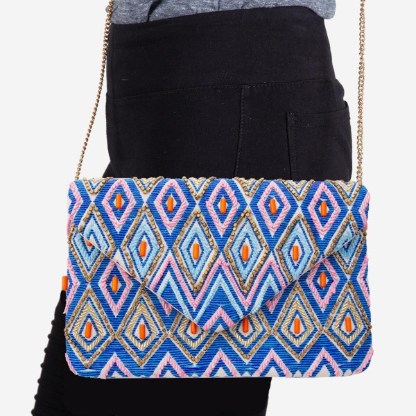 "Pink and Blue Rhombus Woven Crossbody with Raised Seed Bead Details.  - Fold Over Snap Button Closure - One Inside Open Pocket - Lined Inside  - Metal Chain Strap - Hangs approximately 22""   - Approximately 10"" W x 6.5"" T  - 100% Cotton"