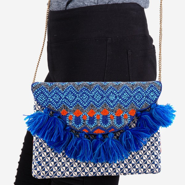 """High Quality Blue Multi Seed Beaded Crossbody Clutch With Tassel Accents  - Lined inside - 1 open functional pocket - Fold over flap button closure - Approximately 10"""" W x 7.5"""" T - Strap hangs 21"""" L - 100% Cotton"""