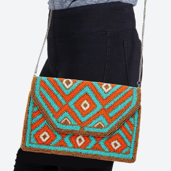"Orange and Turquoise Geometric Seed Beaded Crossbody.  - Fold Over Snap Button Closure - One Inside Open Pocket - Lined Inside  - Metal Chain Strap - Hangs approximately 22""   - Approximately 10.5"" W x 7"" T  - 100% Cotton"
