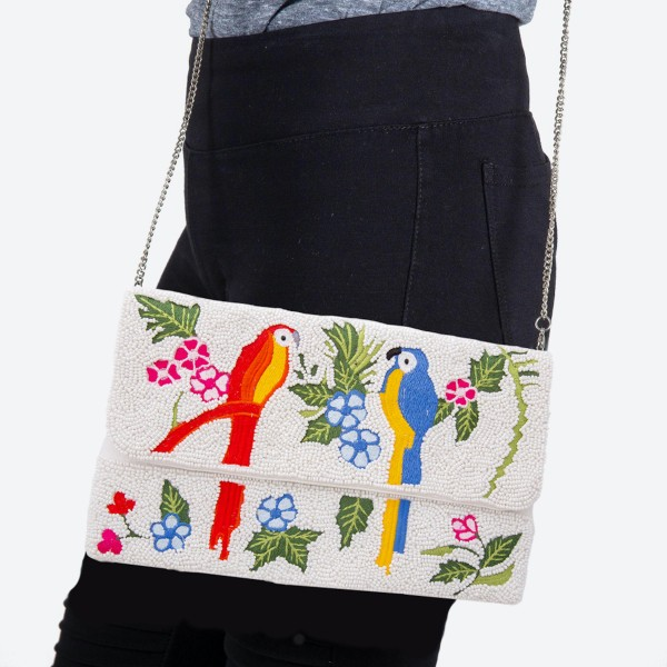 "Seed Beaded Crossbody with Parrot and Floral Embroidered Details.  - Fold Over Snap Button Closure - One Inside Open Pocket - Lined Inside  - Metal Chain Strap - Hangs approximately 22""   - Approximately 10"" W x 6.5"" T  - 100% Cotton"