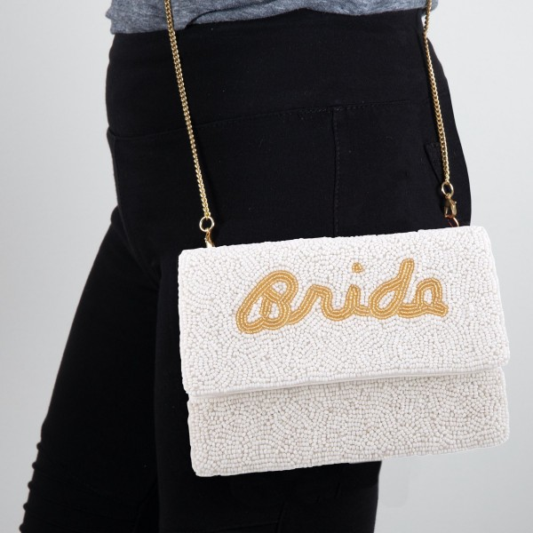 """High Quality Ivory Seed Beaded Crossbody Clutch Featuring The Word """"Bride"""" Embroidered In Gold Cursive  - Lined inside - 1 open functional pocket - Fold over flap button closure - Approximately 7"""" W x 5"""" T - Strap hangs 21"""" L - 100% Cotton"""