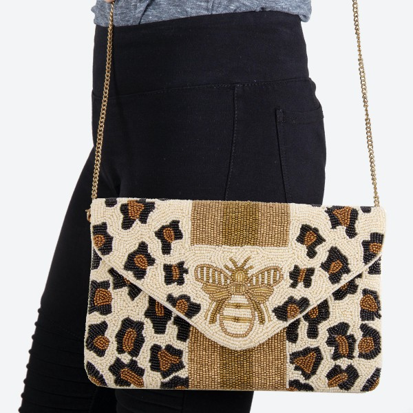 "High quality designer inspired leopard print Bee crossbody clutch.  - Open lined inside  - 1 open functional pocket - Fold over flap button closure - Approximately 10"" W x 6"" T - Strap hangs 21"" L - 100% Cotton"
