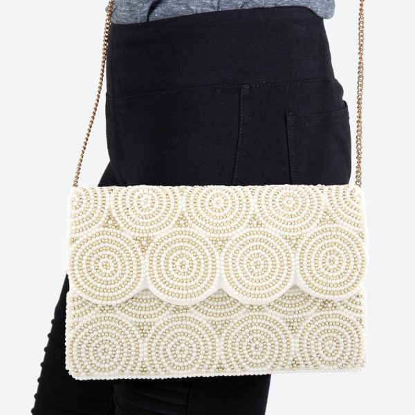 """High Quality Ivory Seed Beaded Crossbody Clutch.  - Lined inside - 1 open functional pocket - Fold over flap button closure - Approximately 10"""" W x 6.5"""" T - Strap hangs 21"""" L - 100% Cotton"""