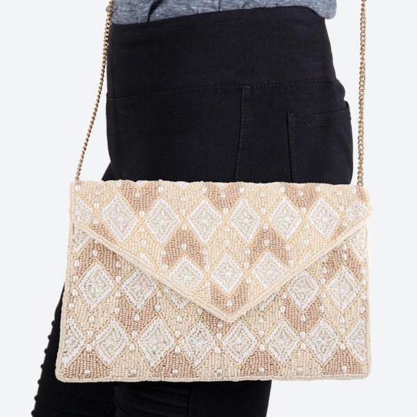 """High Quality Ivory Pearl Geometric Seed Beaded Sequins Crossbody Clutch.  - Open lined inside - 1 open functional pocket - Fold over flap button closure - Approximately 7"""" W x 5"""" T - Strap hangs 22"""" L - 100% Cotton"""