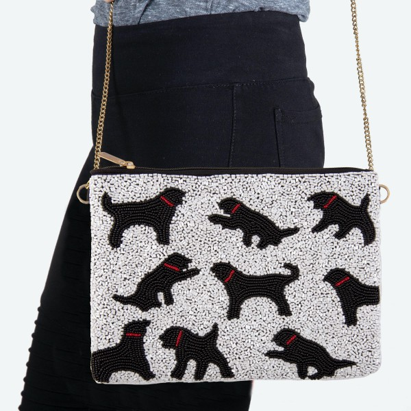"""White Seed Beaded Canvas Crossbody Handbag Featuring Black Dog Print.  - Zipper Closure - One Inside Pocket - Spot Clean Only - Chain Link Strap 21"""" L - Approximately 9"""" W x 7"""" T - 100% Polyester"""