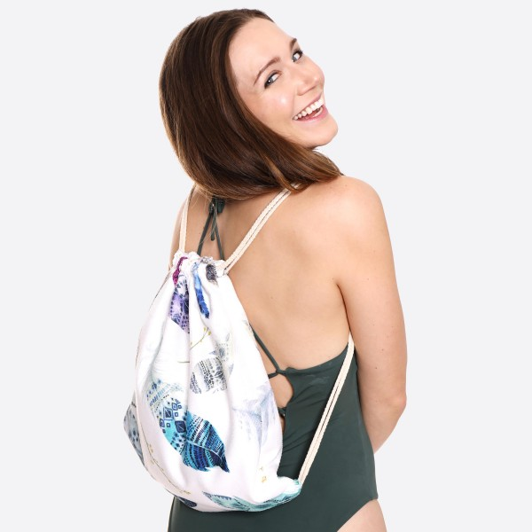 """Feather Print Beach Towel Drawstring Bag All in One.  - Unfold your bag to use the soft beach towel - Conveniently folds back into a drawstring bag - Towel approximately 27"""" W x 59"""" L - 70% Cotton / 30% Polyester"""