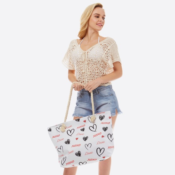 """Love XOXO tote bag with rope handles.  - Open inside pocket - Zipper closure - Rope handles - Approximately 22"""" W x 14"""" T - Handles 12"""" L - 65% Polyester, 35% Cotton"""