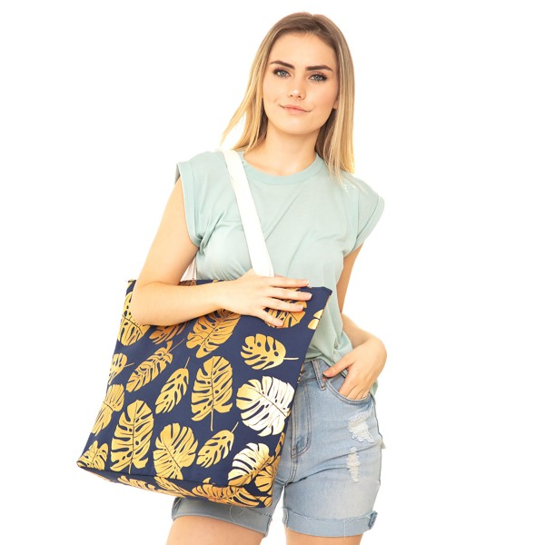 "Navy and Gold Metallic palm leaf print canvas beach bag.   - Button closure  - One inside open pocket  - Approximately 20.5"" W x 16"" T  - Handles hang 12"" L - 60% Cotton, 40% Polyester"