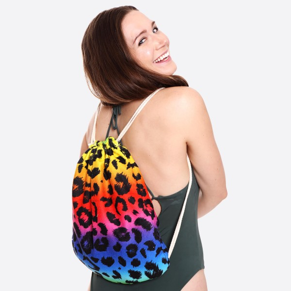 "Rainbow Leopard Print Beach Towel Drawstring Bag All in One.  - Unfold your bag to use the soft beach towel - Conveniently folds back into a drawstring bag - Towel approximately 27"" W x 59"" L - 70% Cotton / 30% Polyester"