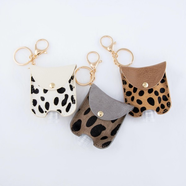 """Keep Your Self Protected While You're Out and About with This Genuine Leather Cow Print Hand Sanitizer Keychain Holder.  - Genuine Leather; Animal Print - Clip to your purse, bag, or diaper bag - Keyring to hold your keys - Fits up to 1fl.oz Sanitizer Bottle - Approximately 3"""" T x 2.5"""" W  ***Hand Sanitizer NOT INCLUDED. (Comes with empty Bottle)"""