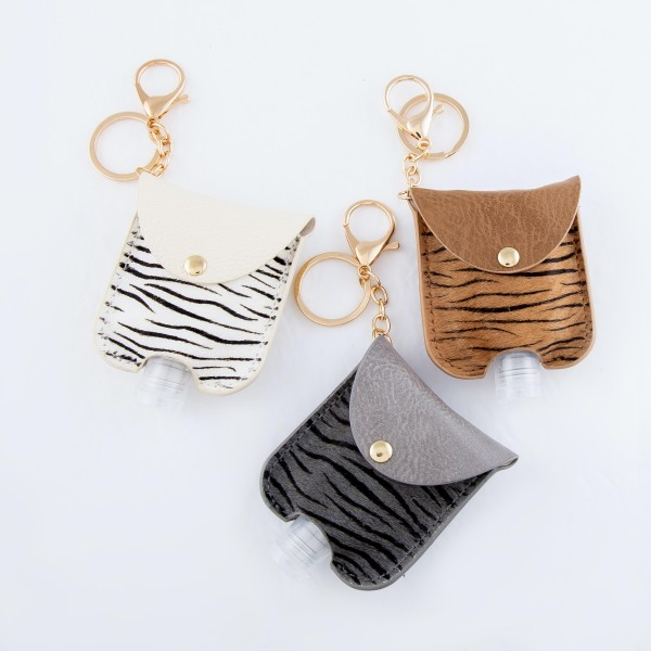 """Keep Your Self Protected While You're Out and About with This Genuine Leather Zebra Print Hand Sanitizer Keychain Holder.  - Genuine Leather; Animal Print - Clip to your purse, bag, or diaper bag - Keyring to hold your keys - Fits up to 1fl.oz Sanitizer Bottle - Approximately 3"""" T x 2.5"""" W  ***Hand Sanitizer NOT INCLUDED. (Comes with empty Bottle)"""