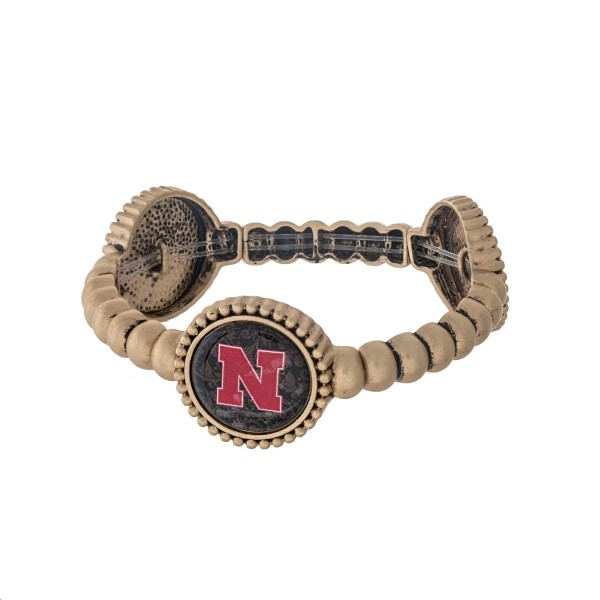 Officially licensed gold tone University of Nebraska stretch bracelet with three stations. Our exclusive design.