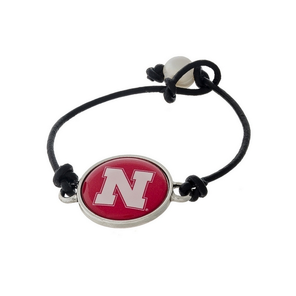 *Our Exclusive Design* Officially licensed University of Nebraska, genuine leather cord bracelet with a freshwater pearl bead closure.