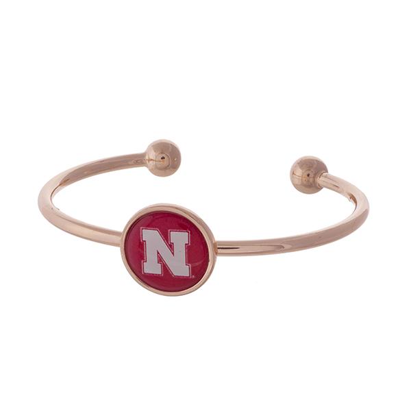 Officially licensed, rose gold tone cuff bracelet with the University of Nebraska logo.