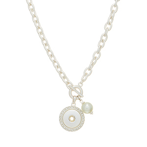 "Matte silver tone toggle necklace featuring a faux ivory pearl and a rhinestone disk with a snap for snap-on charms. Snap jewelry collection. Approximately 17"" in length."