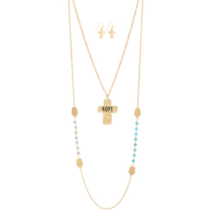 "Worn gold tone layering necklace featuring turquoise and gray beads with cross stations and a hammered cross stamped ""HOPE"". Approximately 35"" in length."