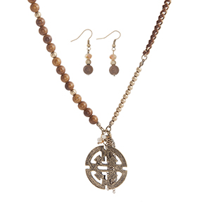 "Burnished gold tone brown beaded necklace set displaying a chain wrapped with brown thread, a metal tassel, and an Aztec medallion. Approximately 33"" in length."