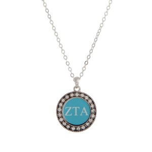 "Silver tone officially licensed Zeta Tau Alpha pendant necklace with rhinestone accents. Approximately 17"" in length."