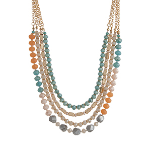 "Gold tone layering necklace displaying strands of turquoise, peach, and ivory glass beads. Approximately 18"" in length."