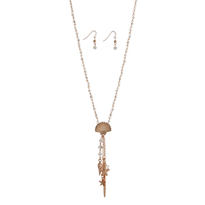 """Gold tone necklace set with white beads displaying a seashell with a hanging cluster of starfish, a shell, and a stick. Approximately 27"""" in length."""