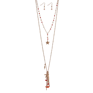 """Gold tone layering necklace set displaying coral and beige beads with a starfish and coral reef charms, hanging chains, and two bars. Approximately 31"""" in length."""