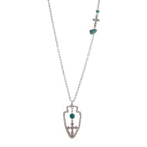 "Burnished silver tone necklace displaying a hammered cross station with a turquoise stone and bead and a wire wrapped arrowhead pendant with a turquoise bead and hanging cross. Approximately 29"" in length."