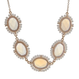 "Gold tone necklace displaying white oval cabochons surrounded by white beads. Approximately 17"" in length."