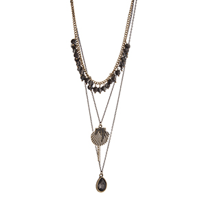 """Gold tone layering necklace displaying black dangling beads, a seashell charm, and a teardrop shape black diamond stone. Approximately 24"""" in length."""