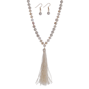 "Ivory beaded necklace with champagne beads and a fabric tassel. Approximately 36"" in length."