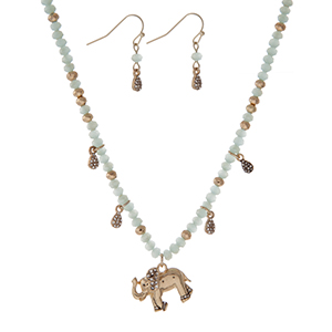 """Gold tone necklace with light blue faceted beads and an elephant pendant. Approximately 18"""" in length."""