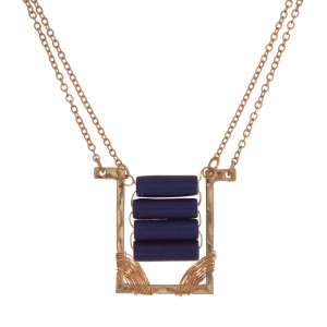 """Dainty gold tone necklace with a rectangle pendant and royal blue beads. Approximately 16"""" in length."""