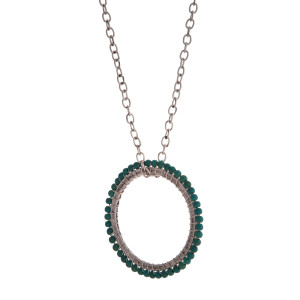 """Silver tone necklace with a turquoise beaded open circle pendant. Approximately 32"""" in length."""