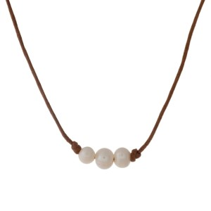 """Tan waxed cord necklace with three cream freshwater pearl beads. Approximately 16"""" in length."""