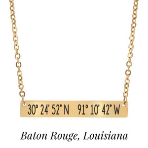 "Gold tone necklace with a bar pendant stamped with the coordinates of Baton Rouge, Louisiana. Approximately 18"" in length."