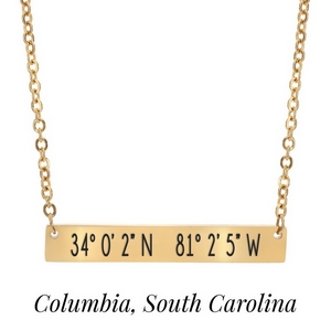 "Gold tone necklace with a bar pendant stamped with the coordinates of Columbia, South Carolina. Approximately 18"" in length."